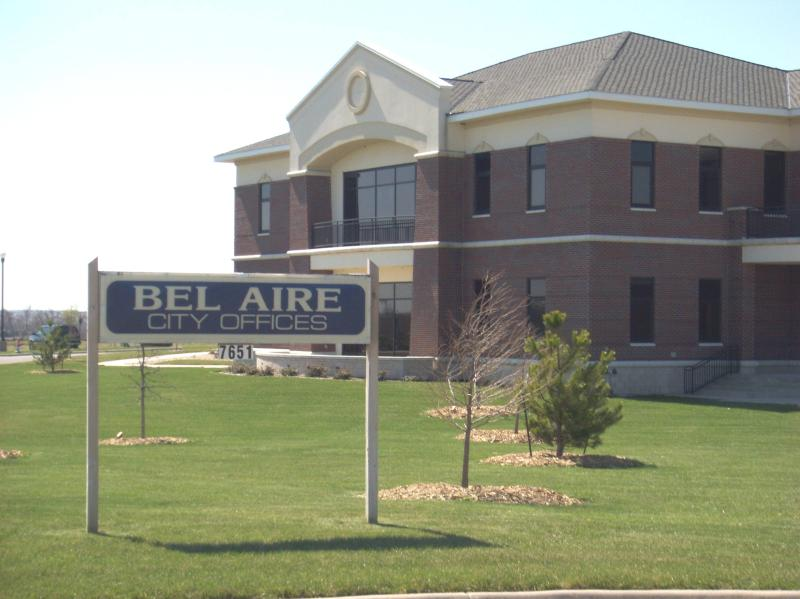 Bel Aire City Hall building with sapling trees planted in the lawn and a sign reading Bel Aire City